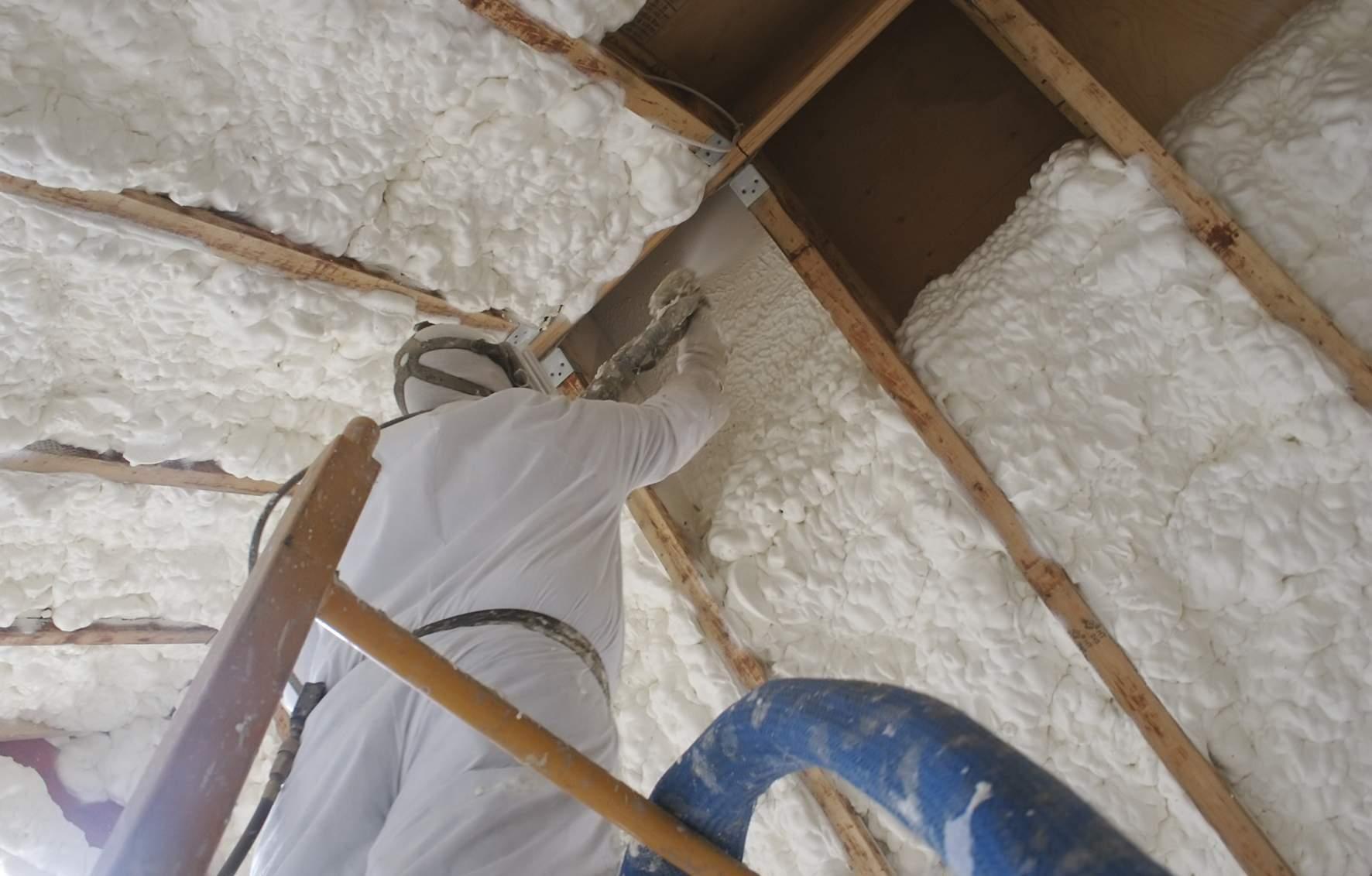 Mężczyzna ocieplający poddasze pianką poliuretanową metodą natrysku piany pod wysokim ciśnieniem