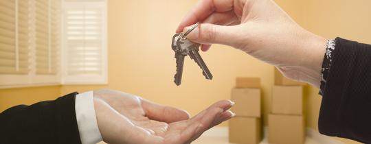 Mężczyzna przekazujący klucze do mieszkania lub domu nowemu właścicielowi.