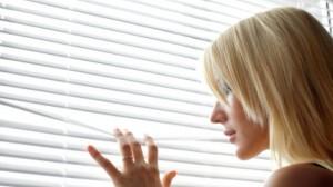 Kobieta stojąca przy oknie z żaluzjami.