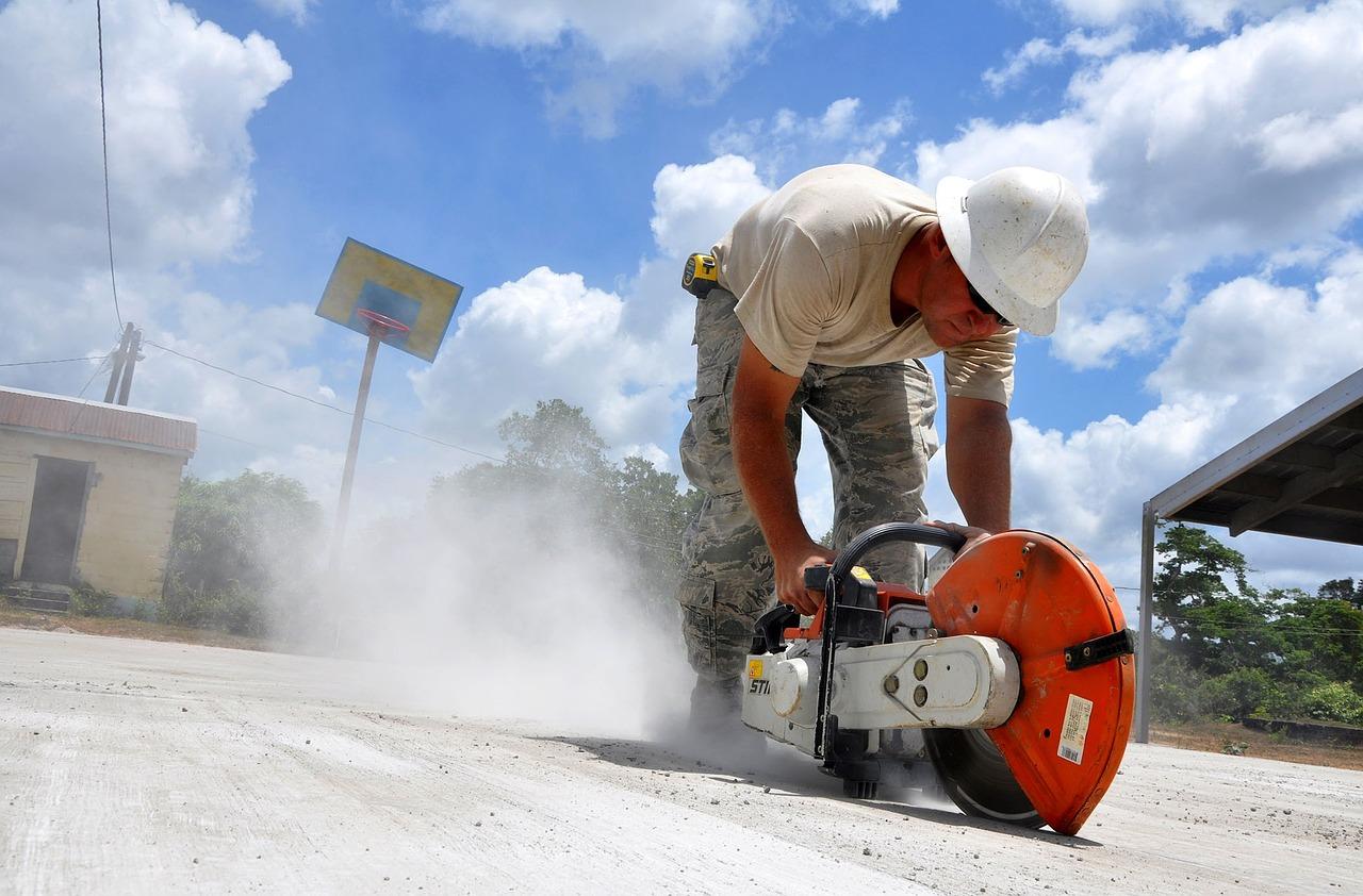 Mężczyzna tnący beton tarczą diamentową.